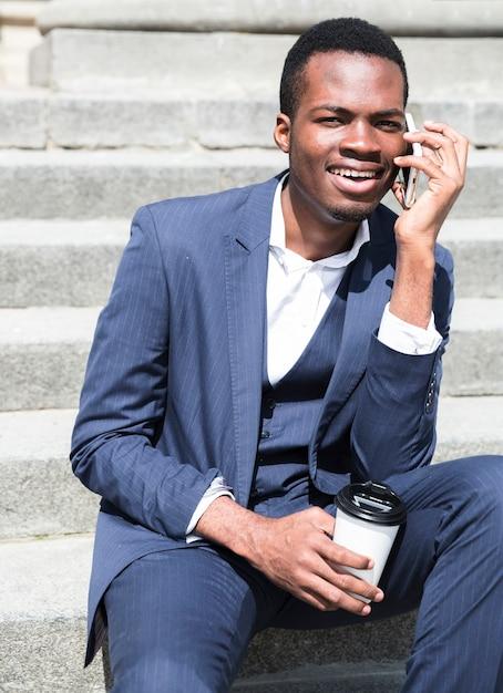Retrato, de, um, jovem, homem negócios, falando passos, segurando, copo café descartável Foto gratuita