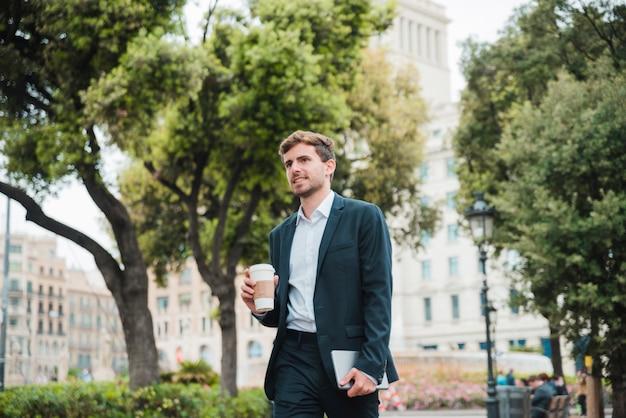 Retrato, de, um, jovem, homem negócios fica, frente, predios, segurando, takeaway, xícara café, e, tablete digital Foto gratuita