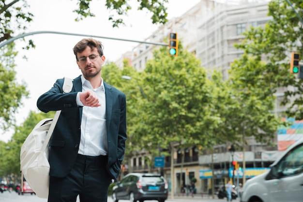 Retrato, de, um, jovem, homem negócios fica, ligado, rua cidade, verificar, a, tempo Foto gratuita