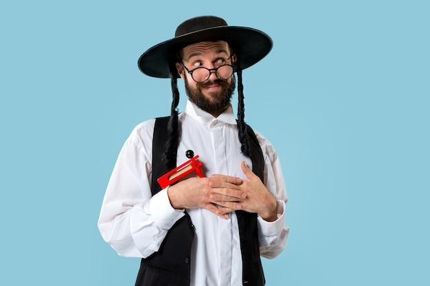 Retrato de um jovem judeu ortodoxo com catraca de madeira durante o festival de purim Foto gratuita
