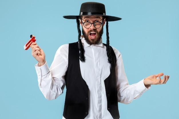 Retrato de um jovem judeu ortodoxo com catraca de madeira grager durante o festival de purim. Foto gratuita