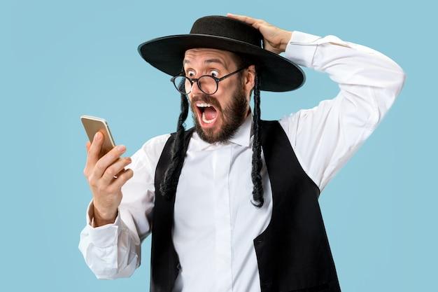 Retrato de um jovem judeu ortodoxo com telefone celular no Foto gratuita