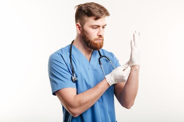 Retrato de um jovem médico concentrado calçar luvas estéreis Foto gratuita
