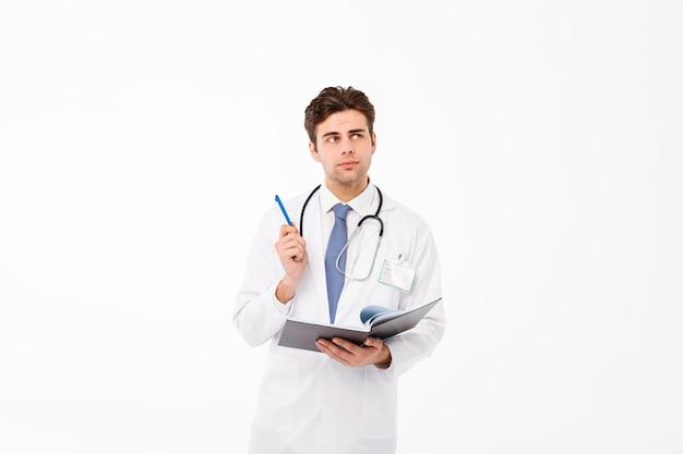 Retrato de um jovem médico masculino pensativo Foto gratuita