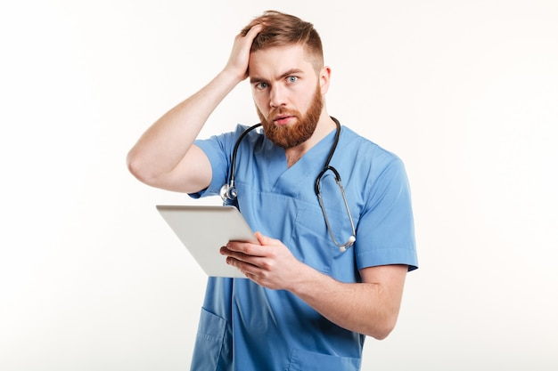 Retrato de um jovem médico surpreso em uniforme azul Foto gratuita