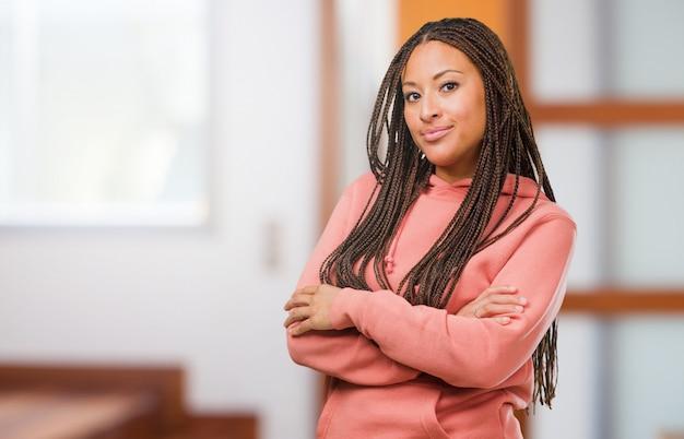 Retrato, de, um, jovem, mulher preta, desgastar, tranças, cruzando seus braços, sorrindo, e, feliz, sendo, confiante, e, amigável Foto Premium