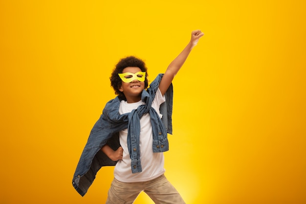 Retrato de um jovem rapaz de raça mista, vestido como um super-herói. bebê preto em traje de super herói. o vencedor e sucesso Foto Premium