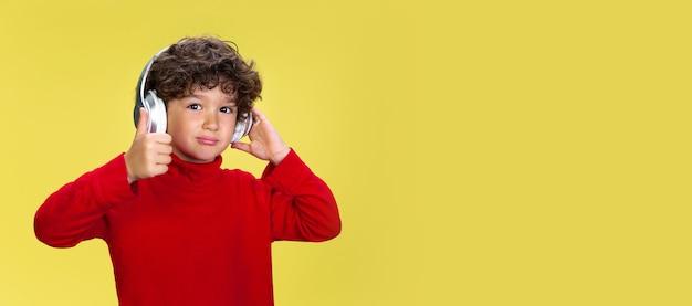 Retrato de um jovem rapaz encaracolado com roupa vermelha em fundo amarelo studio. infância, expressão, educação, conceito divertido. Foto gratuita