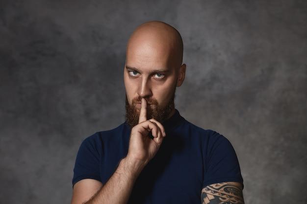 Retrato de um jovem sério tatuado com cabeça raspada e barba espessa com expressão facial estritamente ameaçadora, segurando o fonger na boca, dizendo para ficar de boca fechada Foto gratuita