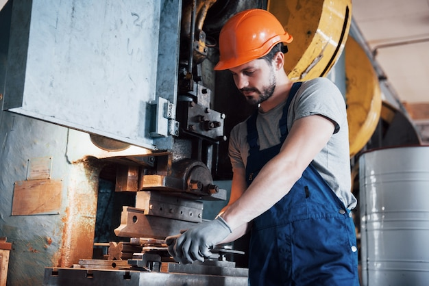 Retrato de um jovem trabalhador em um capacete em uma grande usina de metais. Foto gratuita