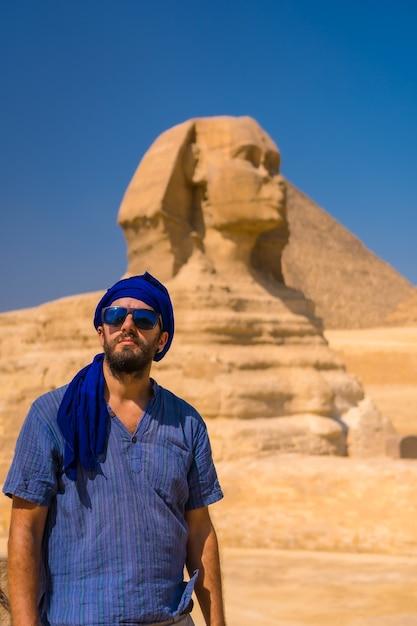 Retrato de um jovem turista vestido de azul e um turbante azul na grande esfinge de gizé. cairo, egito Foto Premium