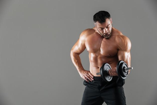 Retrato de um levantamento de fisiculturista masculino sem camisa forte sério Foto gratuita