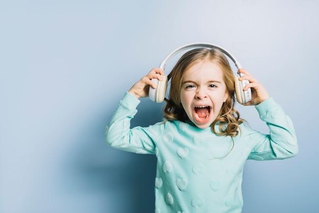 Retrato, de, um, loiro, menininha, com, branca, headphone, ligado, dela, mão, gritando Foto gratuita