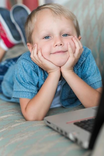 Retrato, de, um, loiro, menino jovem, com, laptop Foto gratuita