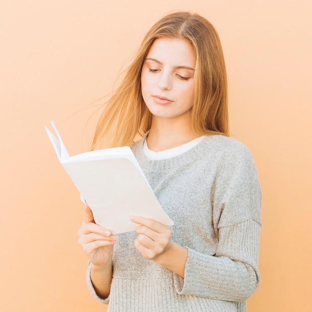 Retrato, de, um, loiro, mulher jovem, livro leitura, contra, pêssego, cor, fundo Foto gratuita