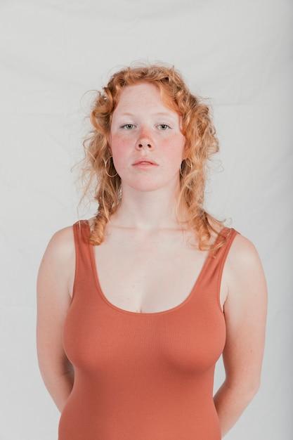 Retrato, de, um, loiro, mulher jovem, olhando câmera, contra, parede cinza Foto gratuita