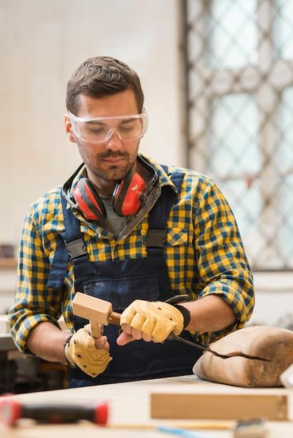 Retrato, de, um, macho, carpinteiro, fazer, madeira, forma, com, cinzel Foto gratuita