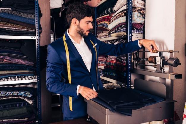 Retrato, de, um, macho, desenhista moda, ajustar, a, tecido, pesando escala, máquina, em, a, oficina Foto gratuita