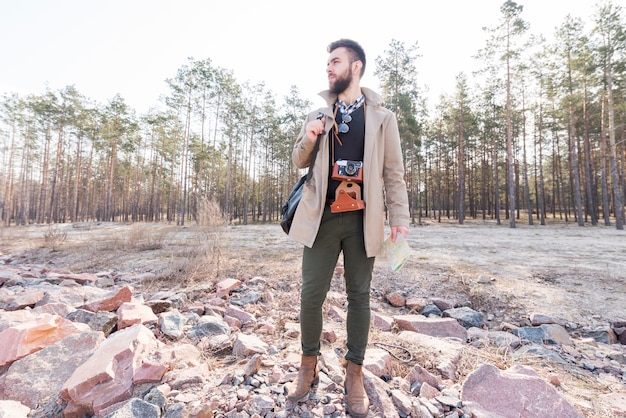 Retrato, de, um, macho, hiker, segurando, um, genérico, mapa, em, a, floresta, olhando Foto gratuita
