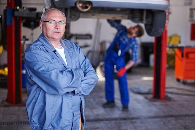 Retrato de um mecânico em uma oficina Foto gratuita