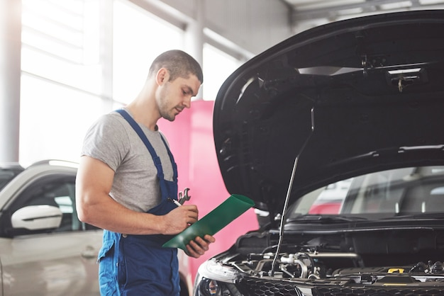 Retrato de um mecânico trabalhando em sua garagem Foto gratuita