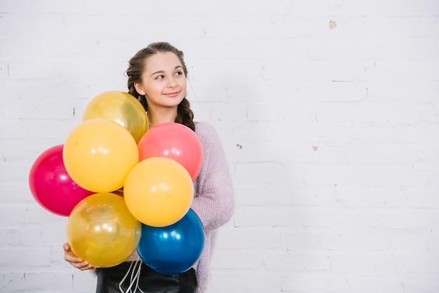 Retrato, de, um, menina adolescente, segurando, balões, em, mão, ficar, contra, parede branca Foto gratuita