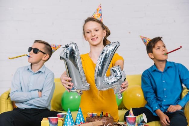 Retrato, de, um, menina aniversário, mostrando, numeral, 14, folha, balloon, com, dela, dois amigos, soprando, partido, chifre Foto gratuita