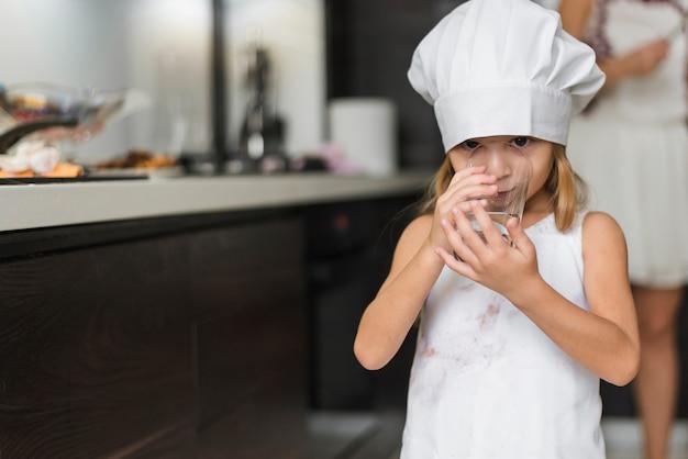Retrato, de, um, menina bonita, desgastar, chapéu cozinheiro, água potável, em, vidro Foto gratuita