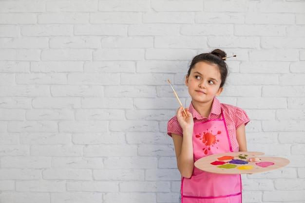 Retrato, de, um, menina, com, pincel, e, paleta, ficar, contra, parede branca Foto gratuita