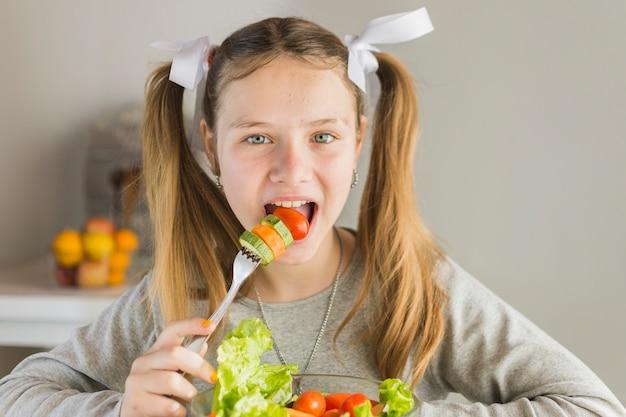 Retrato, de, um, menina, comer, salada vegetal fresca, com, garfo Foto gratuita