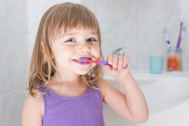 Retrato, de, um, menina, dentes escovando, com, escova de dentes Foto gratuita