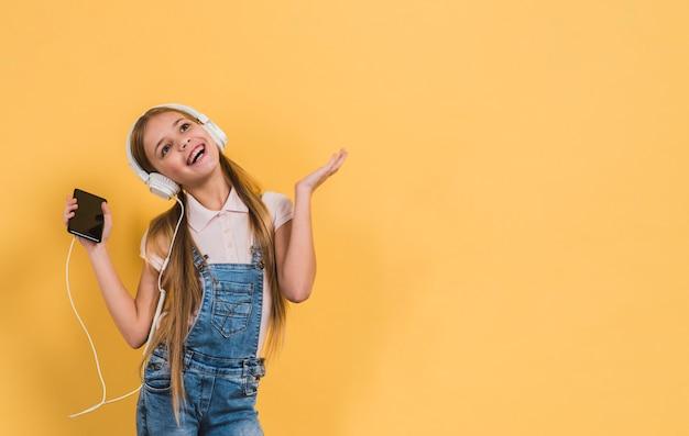 Retrato, de, um, menina, escutar música, ligado, headphone, ficar, contra, experiência amarela Foto gratuita