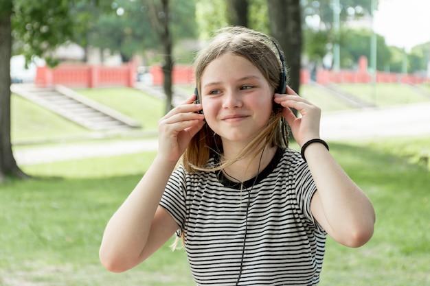 Retrato, de, um, menina jovem sorridente, escutar música, em, parque Foto gratuita