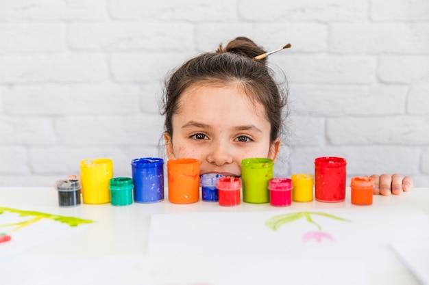 Retrato, de, um, menina, olhar, colorido, pintar garrafas, borda, de, branca, tabela Foto gratuita