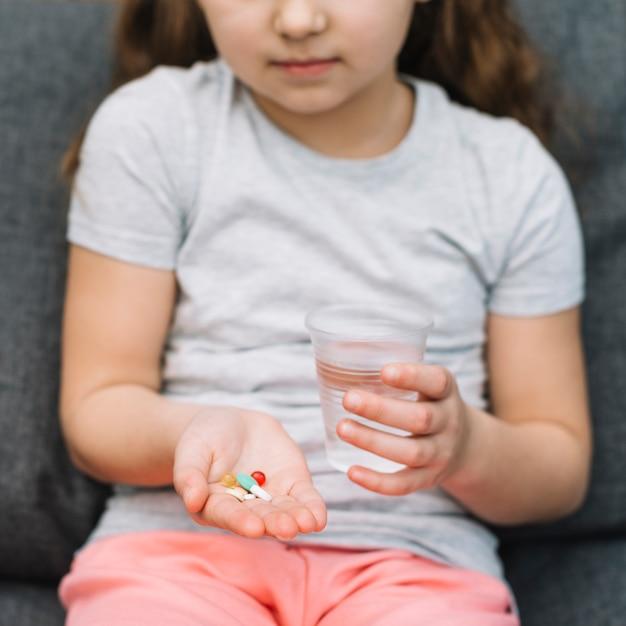 Retrato, de, um, menina, segurando, medicina, e, vidro água, em, mão Foto gratuita