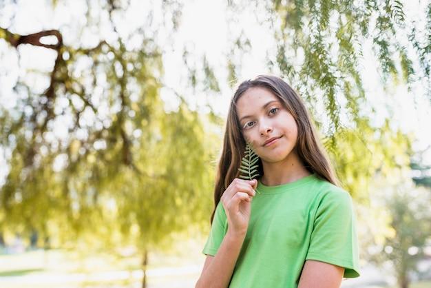Retrato, de, um, menina, segurando, samambaia, em, mão, olhando câmera Foto gratuita