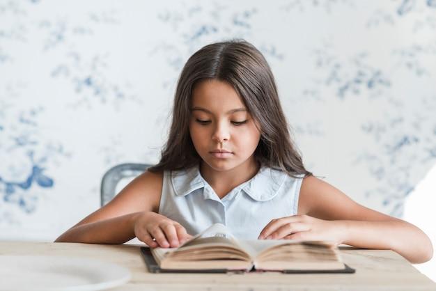 Retrato, de, um, menina sentando, frente, papel parede, livro leitura Foto gratuita