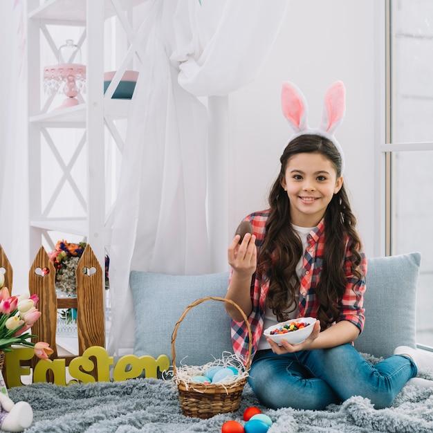 Retrato, de, um, menina sentando, ligado, cama, segurando, ovo chocolate páscoa, e, tigela, bala doce, olhando câmera Foto gratuita