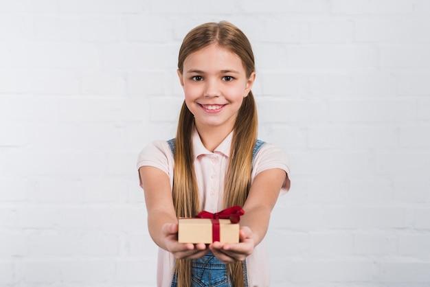 Retrato, de, um, menina sorridente, dar, presente embrulhado, contra, fundo branco Foto gratuita