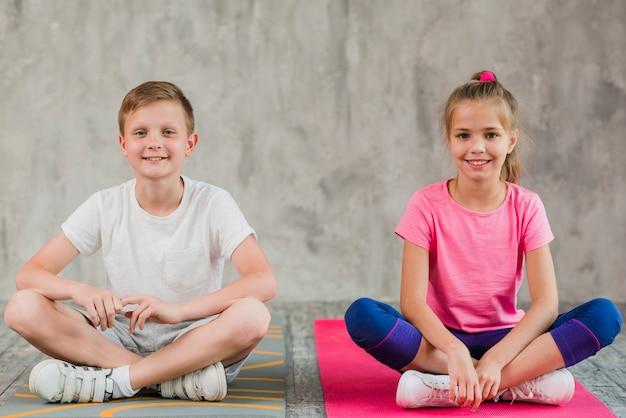 Retrato, de, um, menina sorridente, e, menino sentando, ligado, esteira exercício, com, seu, cruzado, pernas, frente, parede Foto gratuita