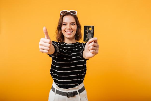 Retrato, de, um, menina sorridente, segurando, cartão crédito Foto gratuita