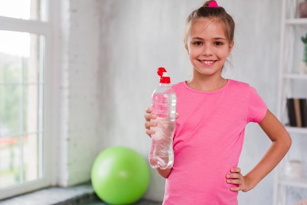 Retrato, de, um, menina sorridente, segurando, garrafa plástico água, em, mão Foto Premium