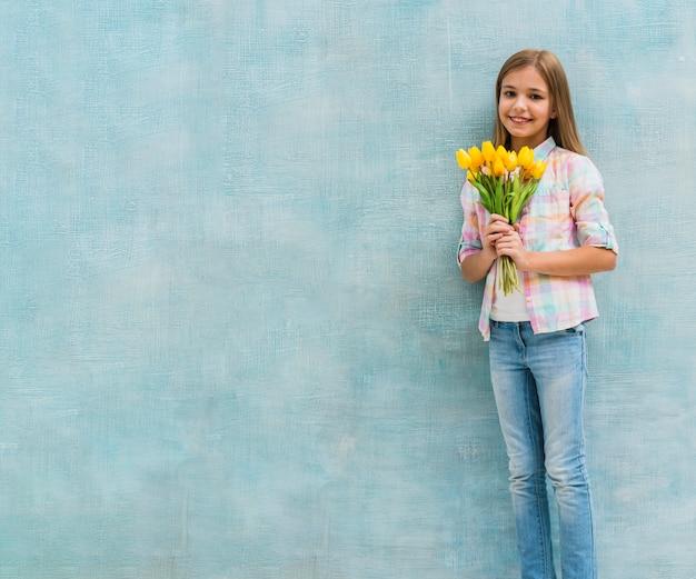 Retrato, de, um, menina sorridente, segurando, tulipa amarela, flores, em, mão, ficar, contra, parede azul Foto gratuita