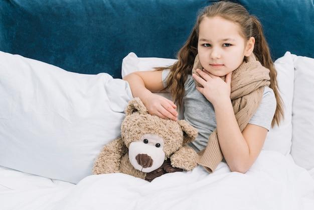 Retrato, de, um, menina, tocar, dela, pescoço, com, mão, localização, com, urso teddy, cama Foto gratuita