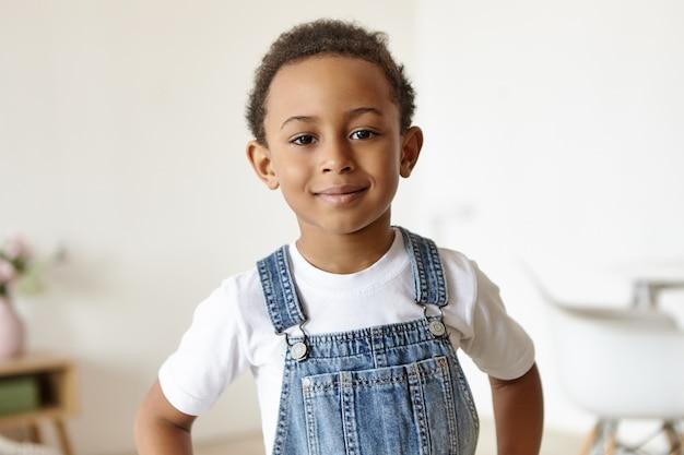 Retrato de um menino bonito e alegre de origem africana posando dentro de casa Foto gratuita