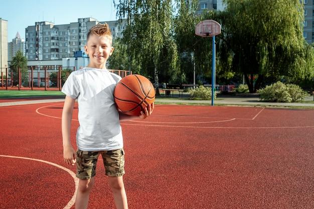 Retrato de um menino com uma bola de basquete em uma quadra de basquete Foto Premium