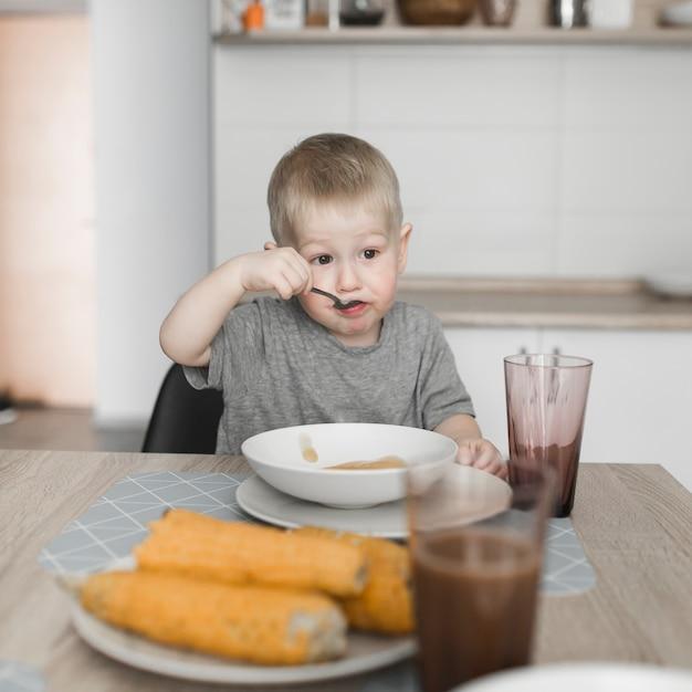 Retrato, de, um, menino, comendo alimento, casa Foto gratuita