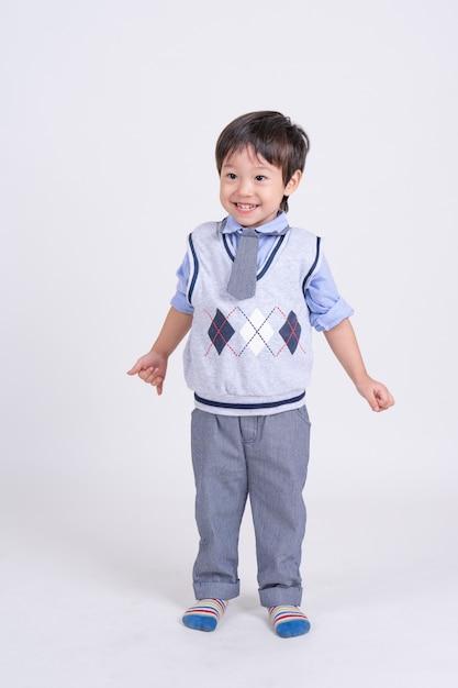Retrato de um menino de pé com sorrindo Foto gratuita