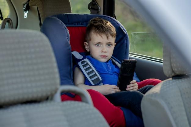 Retrato de um menino entediado sentado em uma cadeirinha. segurança no transporte de crianças. Foto Premium