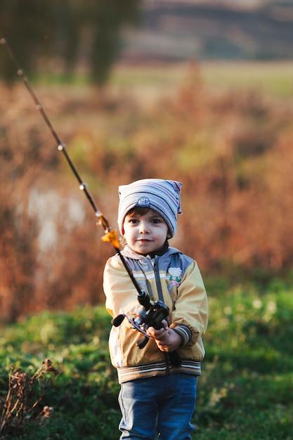 Retrato, de, um, menino, segurando, cana de pesca Foto gratuita